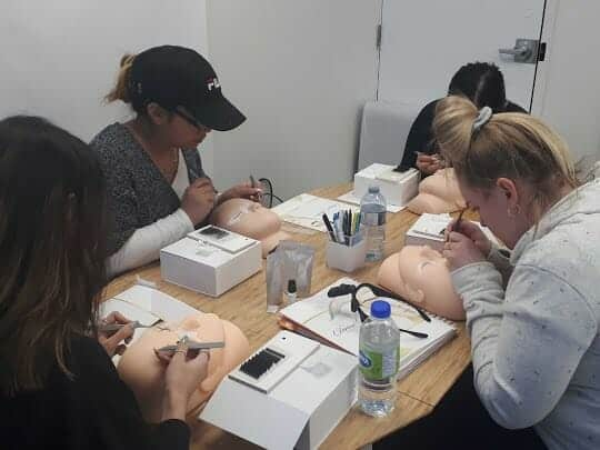 Students working on mannequin head during our eyelash extension course