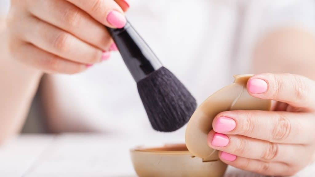 Woman applying foundation with a brush