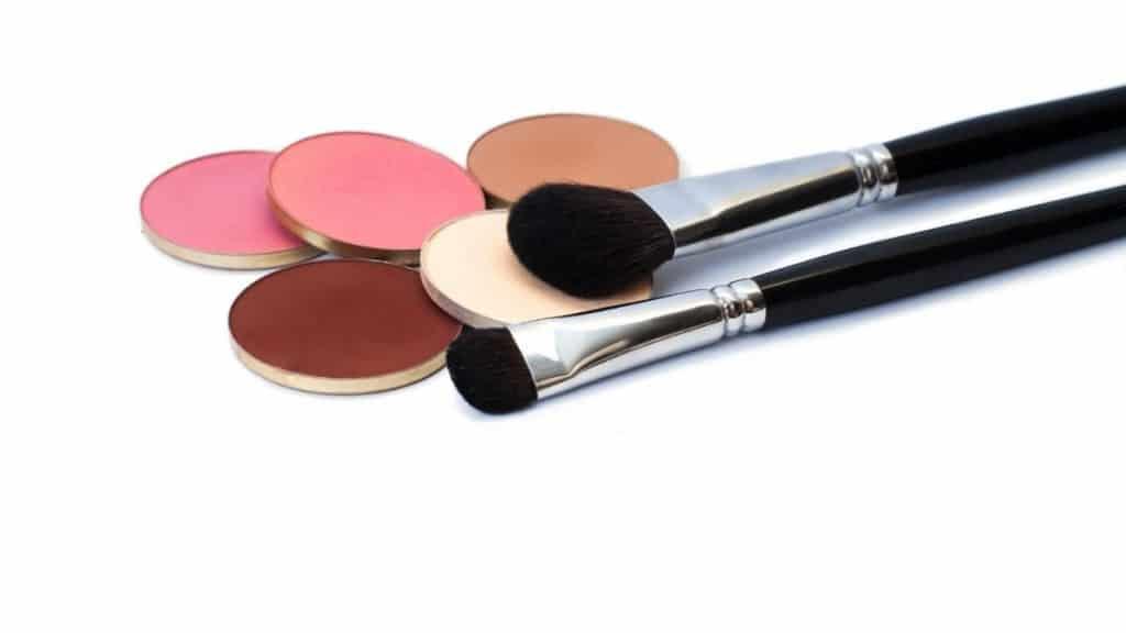 Eyeshadow brushes next to eyeshadow palette