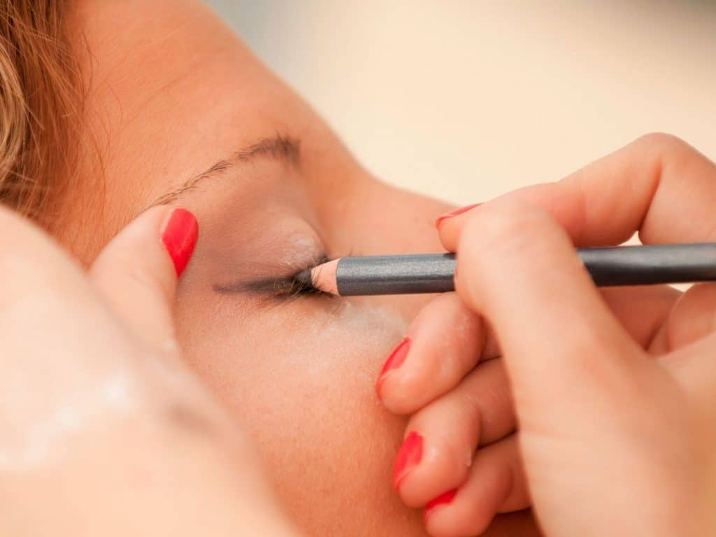 Woman applying pencil eyeliner