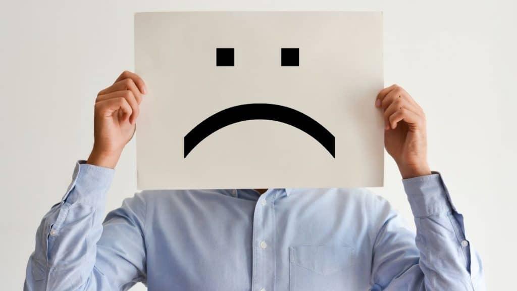 Client satisfaction survey. Man holding unhappy client face.